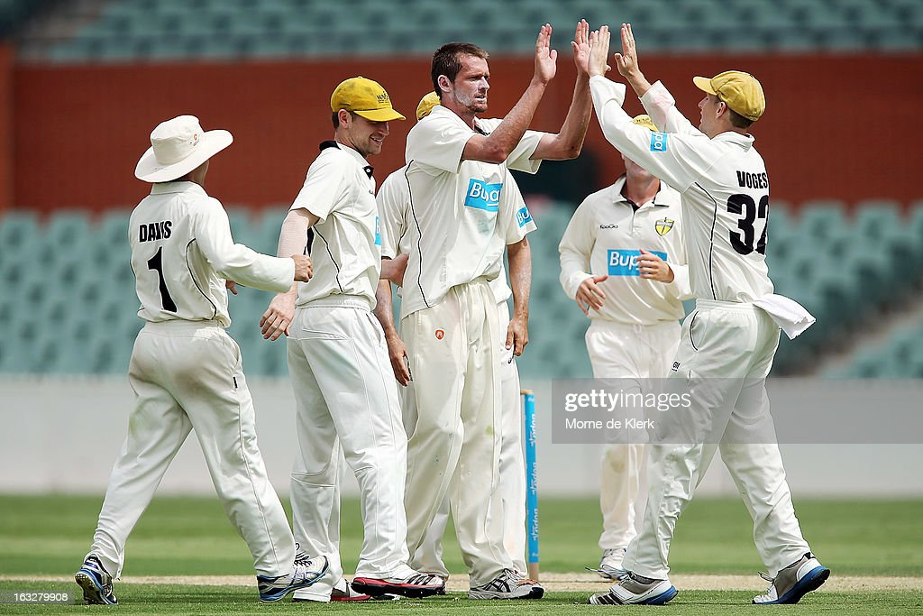 Michael Hogan (C) of the Warriors is congratulated by teammates after he got the wicket of Travis Head of the Redbacks during day one of the Sheffield Shield match between the South Australian redbacks and the Western Australia Warriors at Adelaide Oval on March 7, 2013 in Adelaide, Australia.