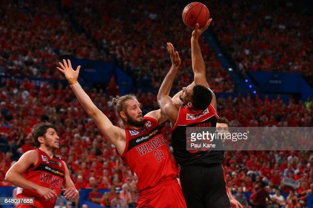 Michael Holyfield of the Hawks puts a shot up against Jesse Wagstaff of the Wildcats during game three of the NBL Grand Final series between the...