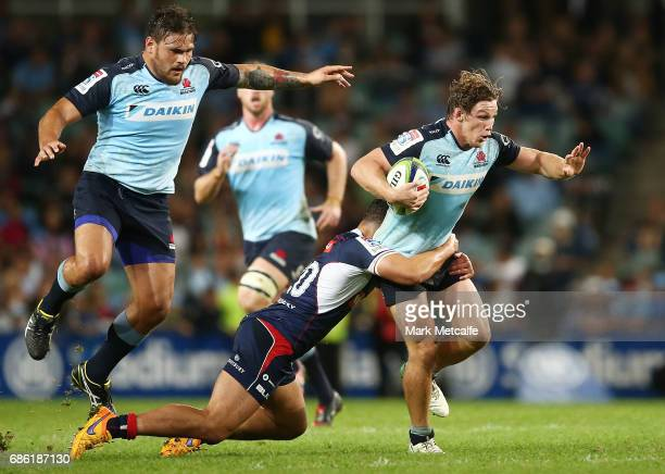 Michael Hooper of the Waratahs is tackled by Colby Fainga'a of the Rebels during the round 13 Super Rugby match between the Waratahs and the Rebels...