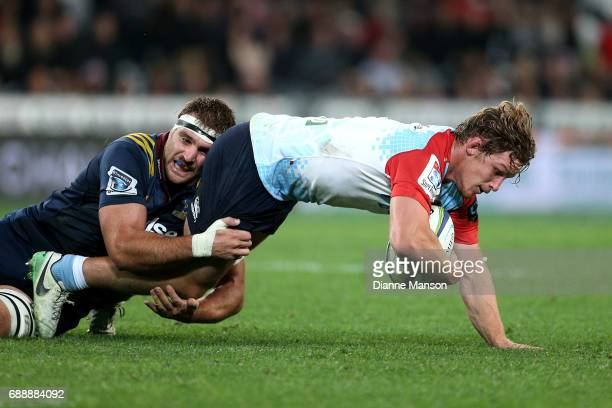 Michael Hopper of the Waratahs tries to break the tackle of Luke Whitelock of the Highlanders during the round 14 Super Rugby match between the...