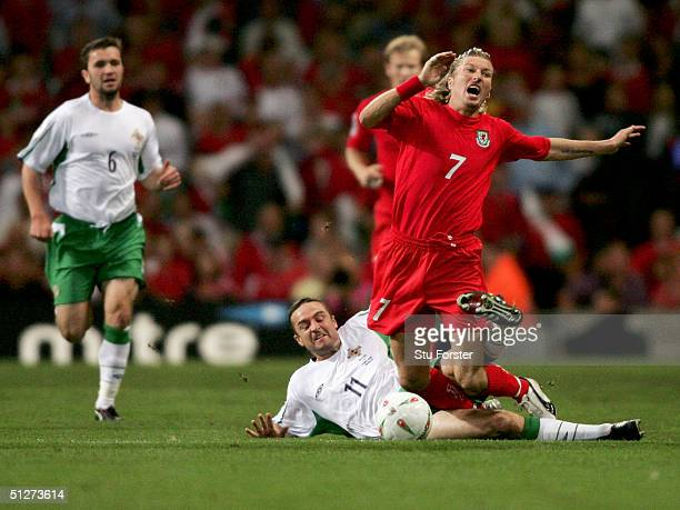 Michael Hughes of Northern Ireland brings down Robbie Savage of Wales as both are sent off during the Group Six World Cup Qualifier between Wales and...