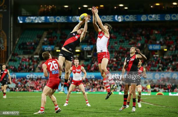 Michael Hurley of the Bombers is challenged by Kurt Tippett of the Swans during the round 19 AFL match between the Sydney Swans and the Essendon...
