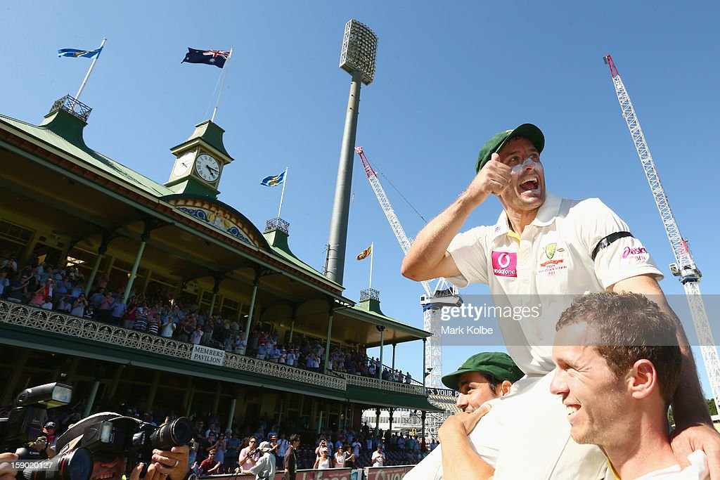 Michael Hussey of Australia gives the thumbs up as he is chaired from the filed by Mitchell Johnson and Peter Siddle after his retirement from international cricket on day four of the Third Test match between Australia and Sri Lanka at Sydney Cricket Ground on January 6, 2013 in Sydney, Australia.