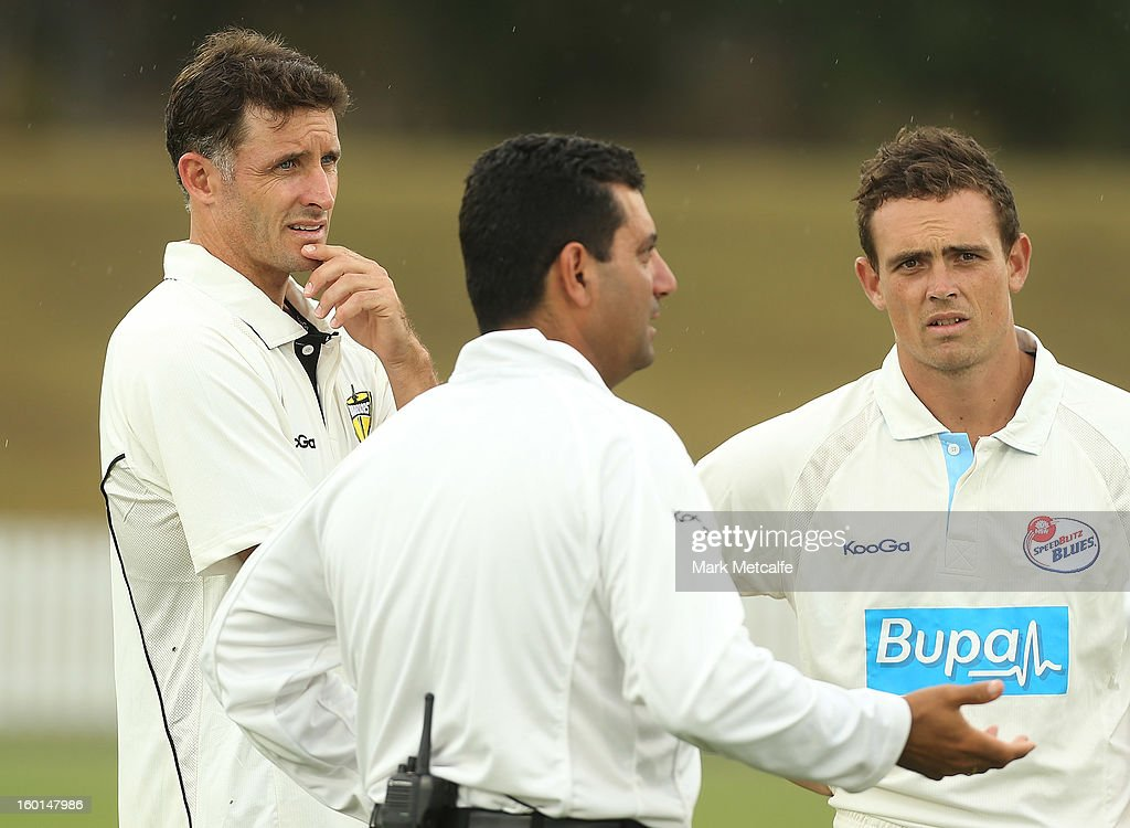 Michael Hussey of the Warriors and Steve O'Keefe of the Blues talk to the umpire as rain delays play on day four of the Sheffield Shield match between the New South Wales Blues and the Western Australia Warriors at Bankstown Oval on January 27, 2013 in Sydney, Australia.