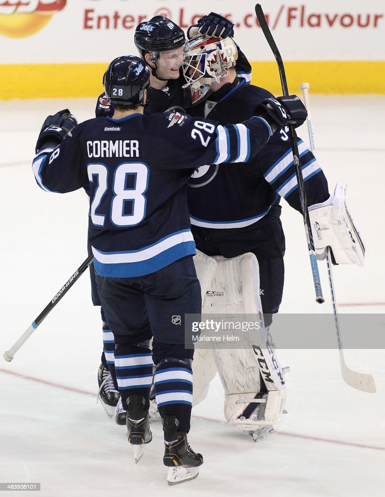 Michael Hutchinson #34 of the Winnipeg Jets is congratulated by teammates Jacob Trouba #8 and Patrice Cormier #28 after his first NHL win in a shootout against the Boston Bruins at the MTS Centre on April 10, 2014 in Winnipeg, Manitoba, Canada.