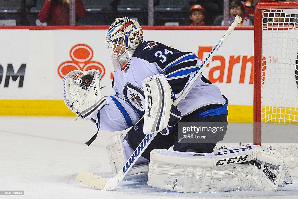 Michael Hutchinson #34 of the Winnipeg Jets makes a glove save against the Calgary Flames during an NHL game at Scotiabank Saddledome on April 11, 2014 in Calgary, Alberta, Canada. The Jets defeated the Flames 5-3.