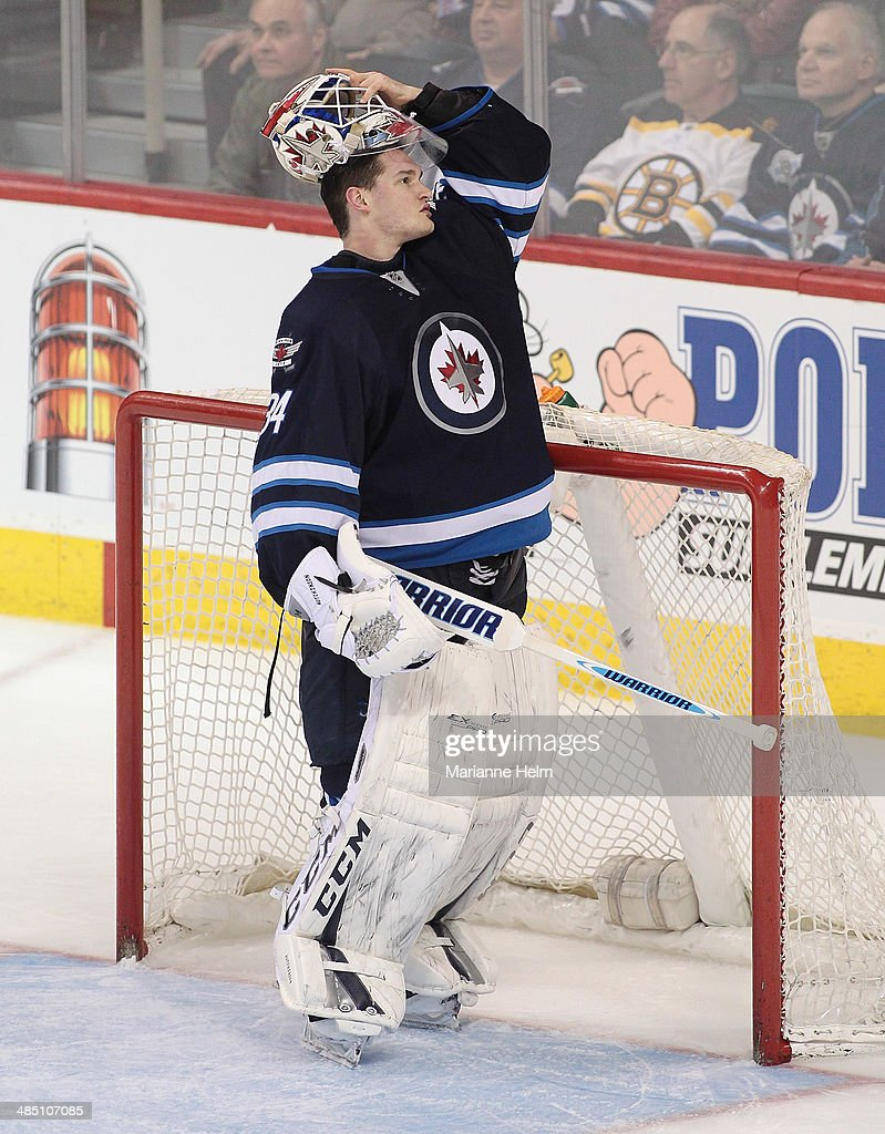 Michael Hutchinson #34 of the Winnipeg Jets puts his helmet back on after a break in the third period of the NHL game against the Boston Bruins at the MTS Centre on April 10, 2014 in Winnipeg, Manitoba, Canada.