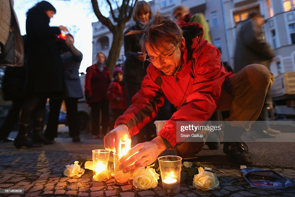 Michael Ickes, who lives nearby, lights candles at Stolpersteine while joing in a commemorative walk in Friedenau district on the 75th anniversary of the Kristallnacht pogroms on November 9, 2013 in Berlin, Germany. Stolpersteine are concrete cobblestones afixed with brass plaques that memorialize local residents who were murdered or expelled by the Nazis during the Holocaust. Events are taking place across Germany today and tomorrow to commemorate the day in 1938 when Nazi gangs across Germany and Austria burned down over 1,000 synagogues, smashed Jewish-owned businesses, looted Jewish residences and killed several hundred Jews. Anti-Semitism was a central component of Adolf Hitler's rise to power and won him wide-spread sympathy among ordinary Germans and Austrians.