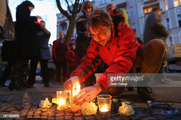 Michael Ickes who lives nearby lights candles at Stolpersteine while joing in a commemorative walk in Friedenau district on the 75th anniversary of...
