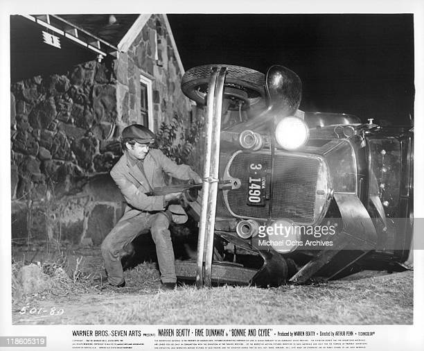 Michael J Pollard with a machine gun near an overturned car in a scene from the film 'Bonnie and Clyde' 1967