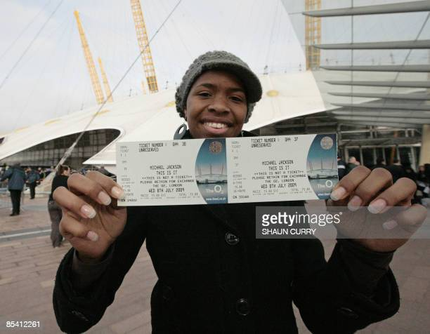 Michael Jackson fan Ayesha Obi poses with the first ticket bought at the O2 Centre in London for one of Michael Jackson's summer concerts in London...