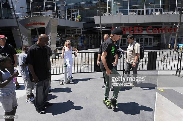 A Michael Jackson fan performs a moonwalk for other fans waiting in line to sign a memorial poster outside Staples Center in Los Angeles on July 4...