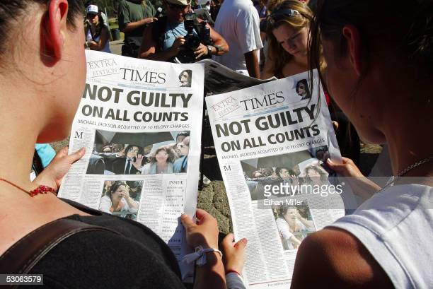 Michael Jackson fans read copies of a special edition of the Santa Maria Times newspaper outside Jackson's Neverland Ranch June 13 2005 in Los Olivos...