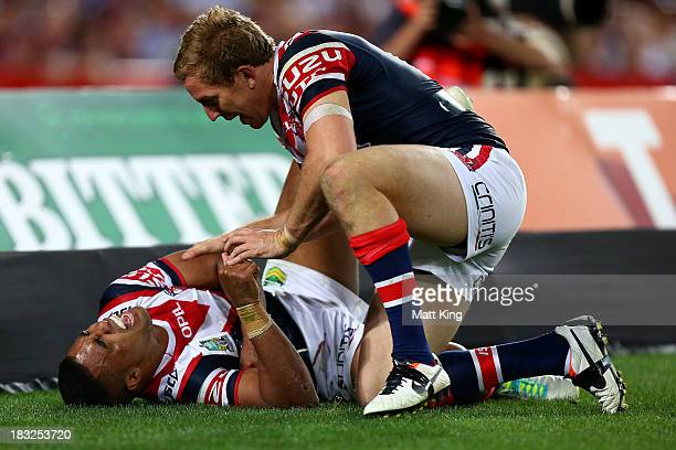 Michael Jennings of the Roosters yells in pain after scoring a try during the 2013 NRL Grand Final match between the Sydney Roosters and the Manly...