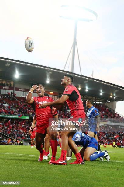 Michael Jennings of Tonga celebrates with teammates after scoring a try during the 2017 Rugby League World Cup match between Samoa and Tonga at...