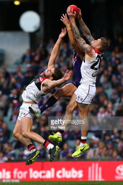 Michael Johnson of the Dockers contests a mark against Josh Bruce and Tim Membrey of the Saints during the round 15 AFL match between the Fremantle...