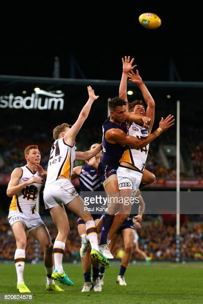 Michael Johnson of the Dockers spoils the marks for Daniel Howe of the Hawks during the round 18 AFL match between the Fremantle Dockers and the...