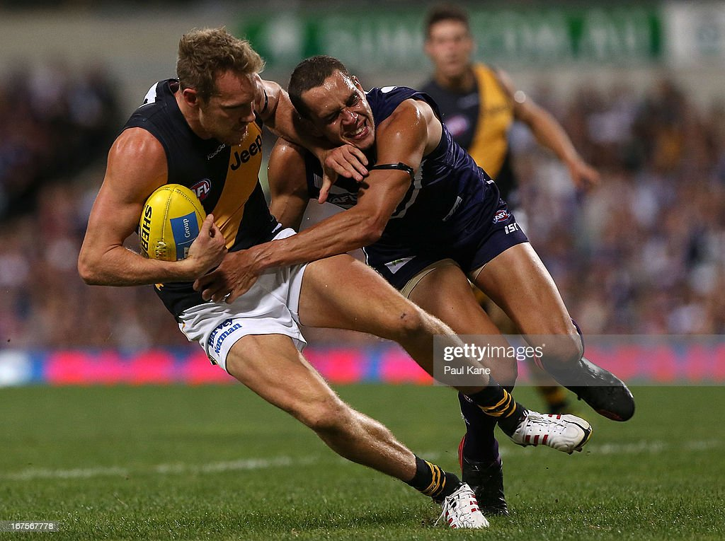 Michael Johnson of the Dockers tackles Luke McGuane of the Tigers during the round five AFL match between the Fremantle Dockers and the Richmond Tigers at Patersons Stadium on April 26, 2013 in Perth, Australia.