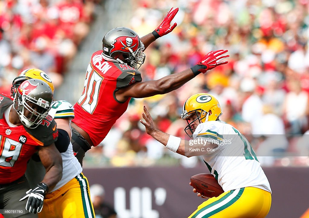 Michael Johnson #90 of the Tampa Bay Buccaneers pressures Aaron Rodgers #12 of the Green Bay Packers and forces a fumble at Raymond James Stadium on December 21, 2014 in Tampa, Florida.