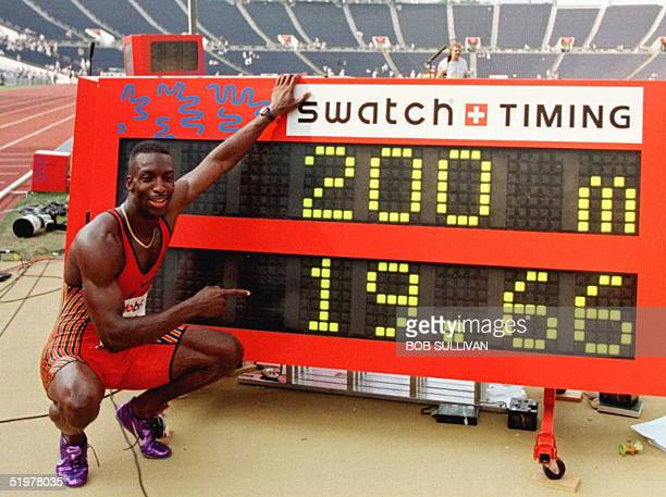 Michael Johnson of the US poses with a track clock displaying his justset world record time in the men's 200 meters 23 June at the US Track and Field...