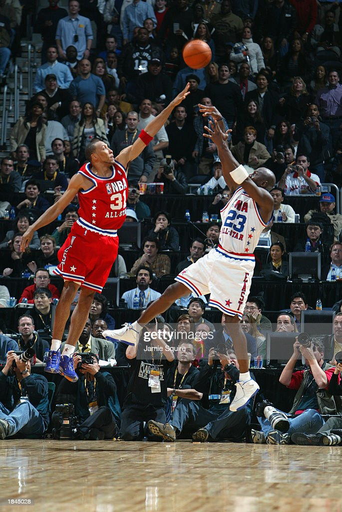 Michael Jordan of the Eastern Conference AllStars puts a shot up over Shawn Marion the Western Conference AllStars to take the game into overtime...
