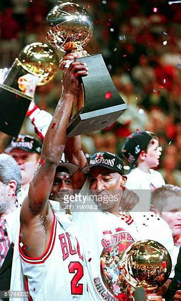 Michael Jordan holds the Larry O'Brien Trophy with teammate Scottie Pippen 13 June after game six of the 1997 NBA Finals at the United Center in...