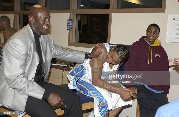 Michael Jordan jokes with Carmelo Anthony of the Denver Nuggets in the locker room after the victory against the Sacramento Kings on April 12 2004 at...