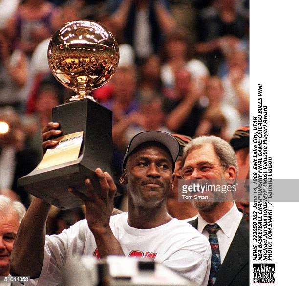 Michael Jordan Lifts Mvp Trophy As Phil Jackson Looks On After Sunday Night's Game 6 Of The Nba Finals At The Delta Center June 14 1998