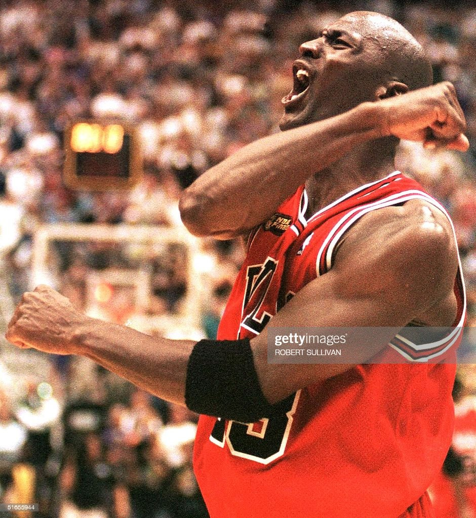 Michael Jordan of the Chicago Bulls celebrates 14 June after winning game six of the NBA Finals against the Utah Jazz at the Delta Center in Salt...