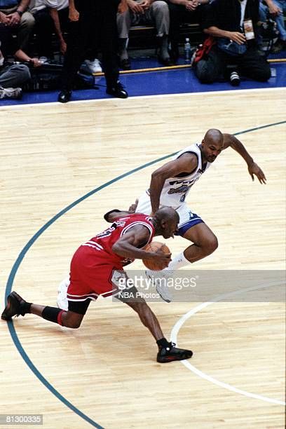Michael Jordan of the Chicago Bulls dribbles past Bryon Russell of the Utah Jazz prior to hitting the game winning jumpshot during game six of the...