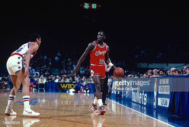 Michael Jordan of the Chicago Bulls dribbles the ball up court guarded by Jeff Malone of the Washington Bullets during an NBA basketball game circa...