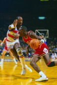 Michael Jordan of the Chicago Bulls drives on Dan Roundfield of the Washington Bullets during an NBA basketball game circa 1986 at the Capital Centre...