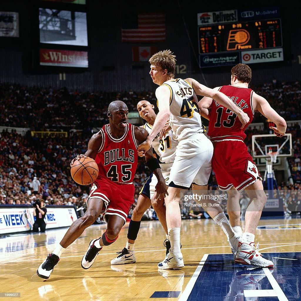 Michael Jordan of the Chicago Bulls drives past Rik Smits of the Indiana Pacers during the NBA game at Market Square Arena on March 19 1995 in...