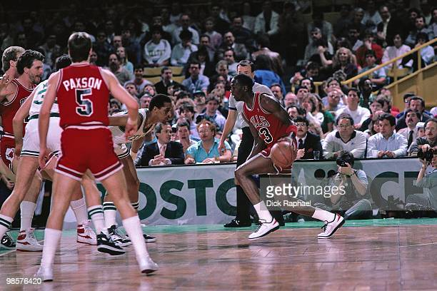 Michael Jordan of the Chicago Bulls drives the ball against Dennis Johnson of the Boston Celtics during a game played in 1987 at the Boston Garden in...