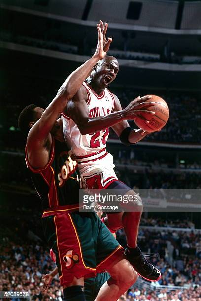 Michael Jordan of the Chicago Bulls drives to the basket and hangs in the air against the Seattle Sonics during Game Two of the 1996 NBA Finals at...
