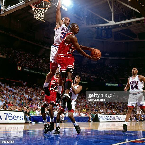 Michael Jordan of the Chicago Bulls drives to the basket for a reverse layup against Charles Barkley of the Philadelphia 76ers during an NBA game...