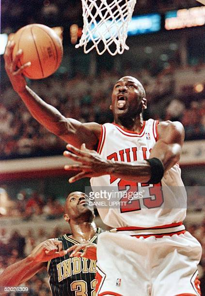 Michael Jordan of the Chicago Bulls drives to the basket past Dale Davis of the Indiana Pacers 17 May during the second half of game one of their NBA...