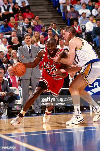 Michael Jordan of the Chicago Bulls drives to the basket while guarded by Chris Mullin of the Golden State Warriors during a game circa 1991 at...