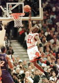 Michael Jordan of the Chicago Bulls flies in for the dunk while Karl Malone of the Utah Jazz watches 10 June during game four of the NBA Finals at...