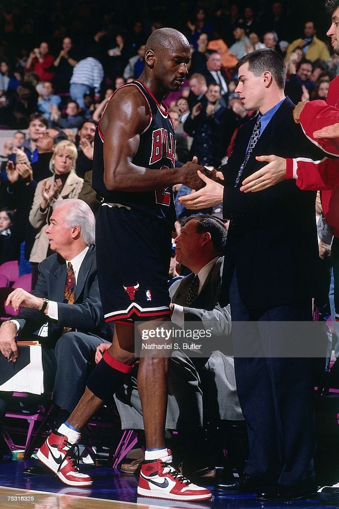Michael Jordan of the Chicago Bulls gets a high five as he walks to the bench wearing his original Nike sneakers against the New York Knicks during...