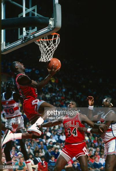 Michael Jordan of the Chicago Bulls goes under the basket for a reverse layup as Manute Bol and Moses Malone of the Washington Bullets looks on...
