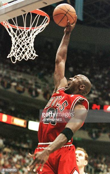 Michael Jordan of the Chicago Bulls goes up for a dunk 05 June beating Adam Keefe of the Utah Jazz in the second half of game two of the NBA Finals...