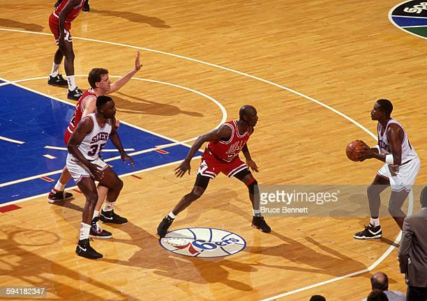 Michael Jordan of the Chicago Bulls guards Ron Anderson of the Philadelphia 76ers as Armen Gilliam of the 76ers battles with Will Perdue of the Bulls...