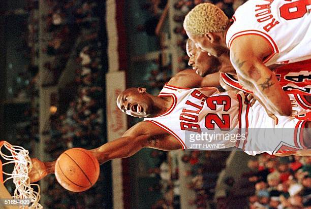 Michael Jordan of the Chicago Bulls hangs on the basket after a slam dunk 20 May as teammate Dennis Rodman and Jamal Mashburn of the Miami Heat watch...