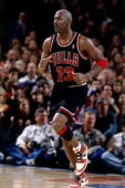Michael Jordan of the Chicago Bulls jogs up court wearing his original Nike sneakers against the New York Knicks during his final game at Madison...