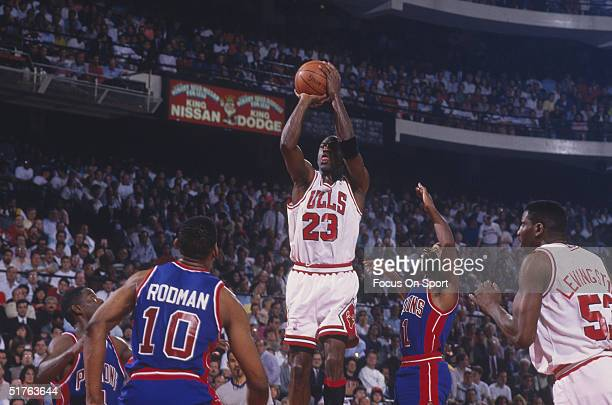 Michael Jordan of the Chicago Bulls jumps to shoot a basket against the Detroit Pistons as Cliff Levingston of the Bulls Dennis Rodman of the Pistons...