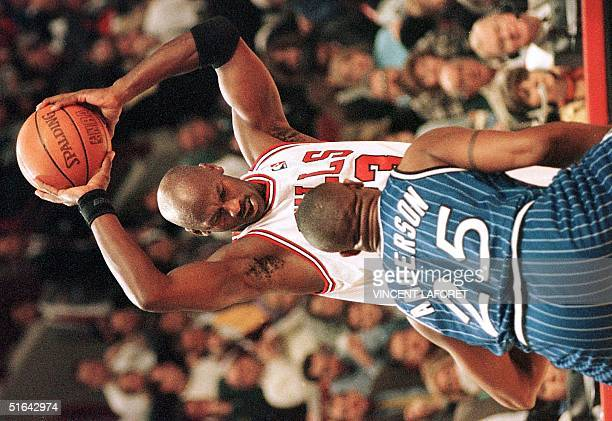 Michael Jordan of the Chicago Bulls looks down at Orlando Magic guard Nick Anderson prior to shooting a basket in the first quarter of the 05...