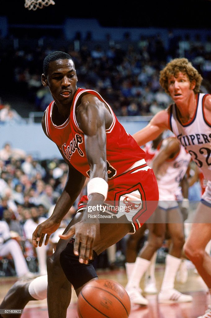 Michael Jordan of the Chicago Bulls moves the ball against Bill Walton of the Los Angeles Clippers during a December 1984 season game at the Sports...
