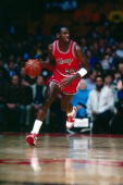 Michael Jordan of the Chicago Bulls moves the ball upcourt during a 1985 season NBA game NOTE TO USER User expressly acknowledges and agrees that by...
