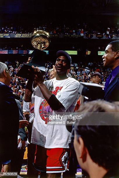 Michael Jordan of the Chicago Bulls poses with his NBA Finals MVP trophy after winning the 1998 NBA Championship after defeating the Utah Jazz in...